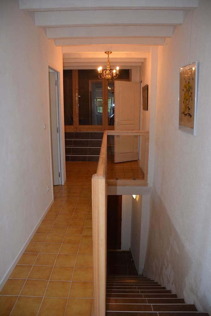 L'escalier depuis la cuisine et le couloir vers la salle d'activités